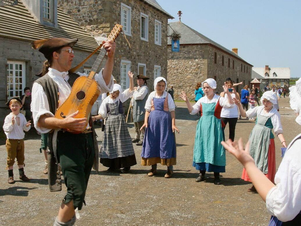 Period actor plays a guitar for others in costume in front of of 18th century building at fortress of louisburg.