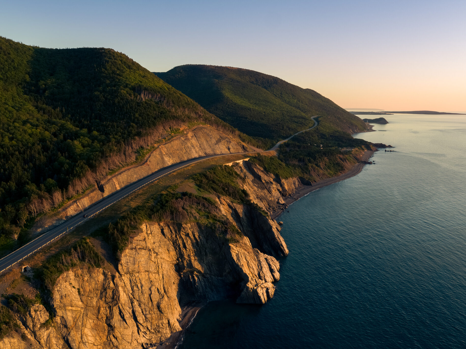 Cap Rouge section of the Cabot Trail with cliffs and ocean lit by the golden glow of a sunset